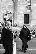 Women wearing muslim çarsaf outside New Mosque in Istanbul.
