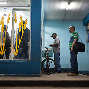Cubans manage their daily life wether waiting, here they wait for rations at a neighborhood bakery. Photography by Jose More