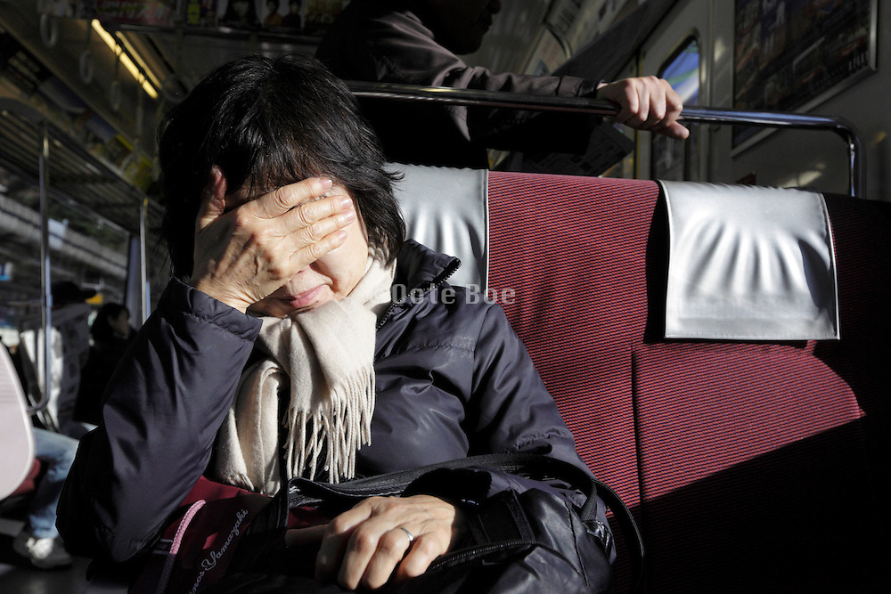 Japanese woman shielding face from strong sunlight