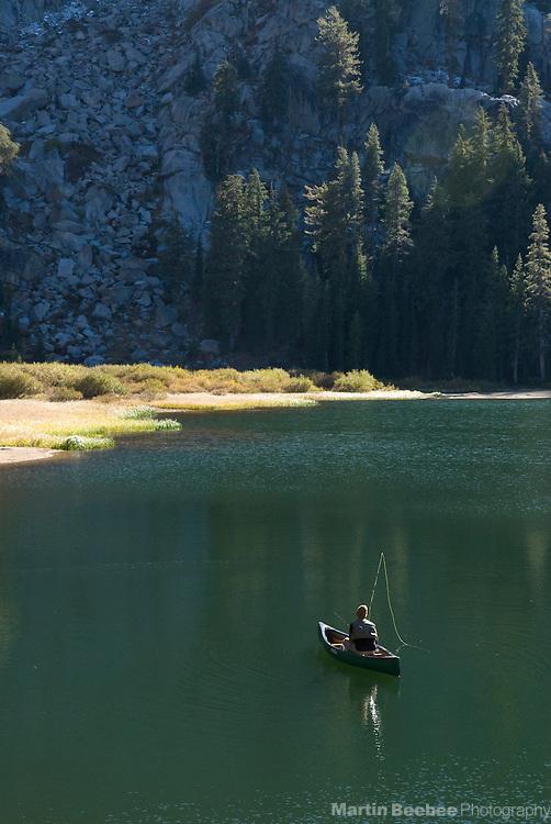 Fisherman in canoe on Woods Lake, El Dorado National Forest, California