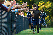 Burlington's Seraphin Iradukunda (front) and the rest of the team high five the crowd after scoring a goal in sudden death overtime during the boys soccer game between the The Burlington Seahorses and the Rice Green Knights at Rice Memorial high School on Tuesday afternoon September 15, 2015 in South Burlington, Vermont. (BRIAN JENKINS/for the FREE PRESS)
