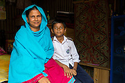 Kohinur with her son in their home in Dhaka, Bangladesh. Kohinur is a garment worker living and working in Dhaka Bangladesh.