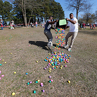 Thomas Wells | BUY at PHOTOS.DJOURNAL.COM<br /> University of Mississippi students Justin Hurd, left, of Grenada and Terry Caldwell of Wilmington, North Carolina fnd it faster to just dump out all the Easter Eggs and then spread them out before Saturday's hunt at Ballard Park.