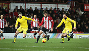 Brentford midfielder John Swift dribbling between two Leeds players during the Sky Bet Championship match between Brentford and Leeds United at Griffin Park, London, England on 26 January 2016. Photo by Matthew Redman.