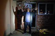 A group of people (some of whom were gang members) who were trespassing are instructed to exit a vacant house with their hand up. Dec. 10, 2011. Oxnard, Calif. (Photo by Gabriel Romero ©2011)