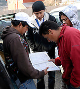 NEWS&GUIDE PHOTO / PRICE CHAMBERS.From left, Cesar Marquina Corona, Hugo Marquina Corona, Gregorio Cruz and Juan Carlos Morales pour over a road atlas just before leaving on a 3,000 mile trip home to Tlaxcala, Mexico. The group travels in a caravan of six mexicans in four cars, hoping for safety in numbers and a fast route to the border.