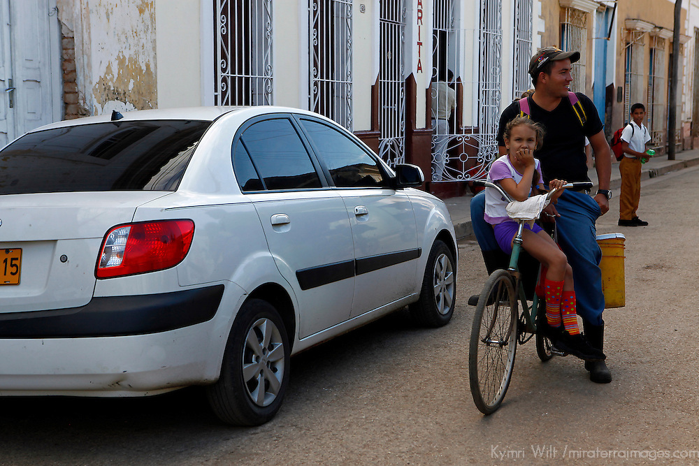 Central America, Cuba, Remedios. A Cuban father and his daughter ride a bicycle in Remedios.