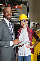 Portrait of female industrial worker standing with male inspector