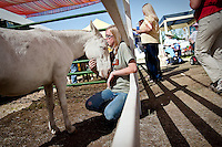 JEROME A. POLLOS/Press..Elina Sasser, 17, leans against a fence as Dudley Do-Bray the mini mule nudges her Friday.
