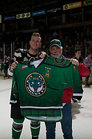 KELOWNA, CANADA - MARCH 18: Gordie Ballhorn #4 of the Kelowna Rockets hands over his St Patricks Day jersey to a winning fan  on March 1, 2018 at Prospera Place in Kelowna, British Columbia, Canada.  (Photo by Marissa Baecker/Shoot the Breeze)  *** Local Caption ***