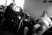 Kenneth Burland, who perfers to be called Kenny, spends time during Christmas morning of 2003, playing solitare on the computer and  talking to his friend and roommate John.