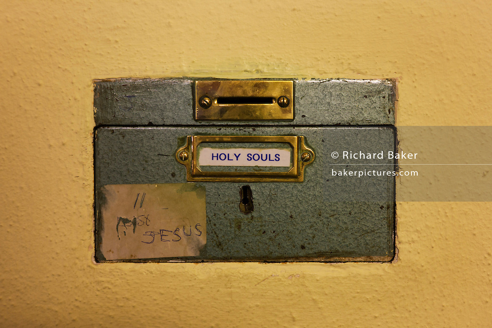 Locked donations box set in wall of St. Lawrence's Catholic church in Feltham, London.