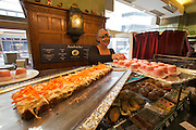 Vienna. Zum schwarzen Kameel. Erna Lenhardt serving to clients at the sandwich counter.