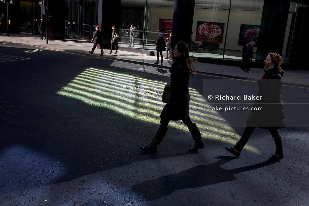 Two women pedestrians walk through green reflected light shining from a City of London office building.