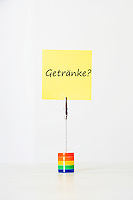 Sticky notepaper with German text meaning Drinks clipped to a multicolored card holder