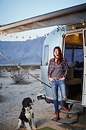 A woman and her dog sit near the doorstep of thier Airstream trailer while camping in the desert of Anza Borrego, California.