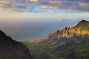 The setting sun lights up the rugged walls of the Kalalau Valley, located on Kauai's Na Pali coast. The cliffs that line the valley are more than 2,000 feet tall.
