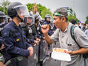 24 NOVEMBER 2012 - BANGKOK, THAILAND: An anti-government protester confronts Thai riot police during a large anti government, pro-monarchy, protest  on November 24, 2012 in Bangkok, Thailand. The Siam Pitak group, which sponsored the protest, cited alleged government corruption and anti-monarchist elements within the ruling party as grounds for the protest. Police used tear gas and baton charges againt protesters.       PHOTO BY JACK KURTZ