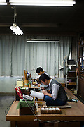 Artisans painting on enamel. Ando Cloisonne, Nagoya, Aichi Prefecture, Japan, February 26, 2018. Family-owned and run Ando Cloisonne was founded in the 1880s and is the only large manufacturer of cloisonne metalware left in Japan. The cloisonne enamelling process is technologically complex and a single work may feature over 50 colours.