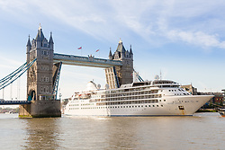 © Licensed to London News Pictures. 01/08/2017. LONDON, UK.  Silver Wind, a huge 514 feet long, 17,400 ton cruise liner leaves London under Tower Bridge this morning after a brief visit, towed backwards by two tugs. Silver Wind carries just 296 passengers and its owner, Silversea claim that the ship has amongst the highest space-to-guest ratios in the cruise ship industry, with the largest suites measuring 1,314 square feet. Tickets cost thousands of pounds, but all guest expenses, even champagne are included in the price. Environmentalists claim the pollution created by giant cruise ships outweigh their economic benefits. The Port of London Authority (PLA) are conducting a work programme during 2017 to monitor air quality and pollution caused by river traffic on the River Thames.  Photo credit: Vickie Flores/LNP