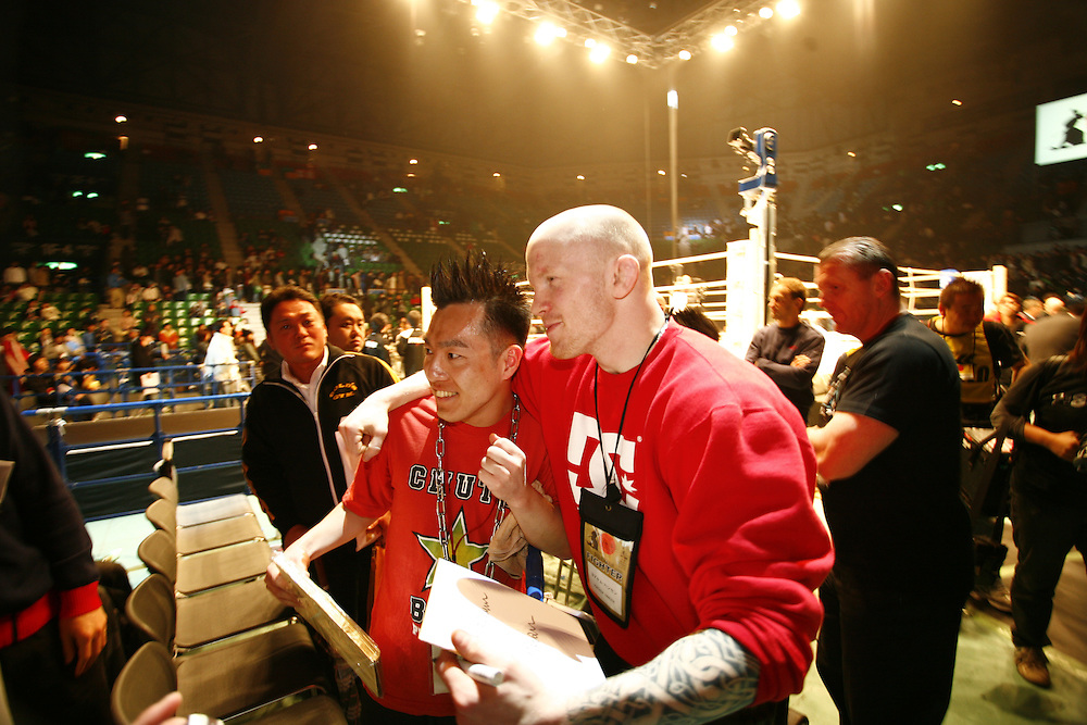 Fighter Joachim Hansen Poses with fan after  fight BUSHIDO Extreme Martial Art fighting Rules are quite limited and fights usually carry on past the bloody nose stage.  It's  very popular in Japan, goes out on primetime TV, fighters get paid as much as 4 million US Dollars a fight and are seen as celebs. Crowd consist of young families, couples etc. Piece will look at why sport is so successful in Japan, appealing to so called 'lost generation' of young people suffering from effects of collapse of economy/rise of unemployment.