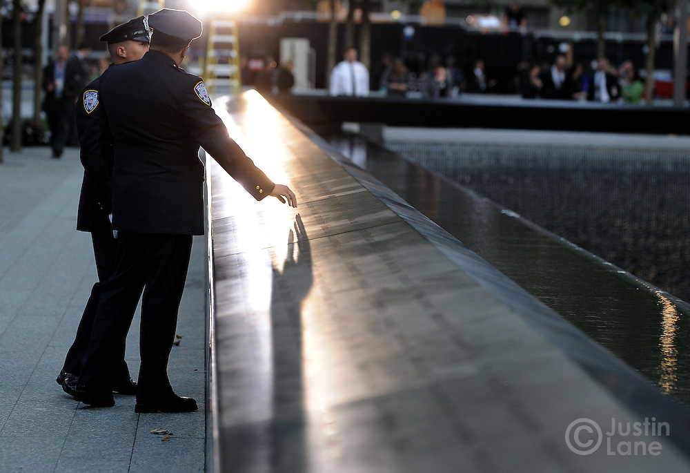 A Port Authority police officer reaches to to touch the names inscribed around the North Pool of the 9/11 Memorial during tenth anniversary ceremonies at the site of the World Trade Center September 11, 2011, in New York. POOL/Justin Lane/EPA
