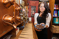 Portrait of female salesperson showing fresh coffee beans in store