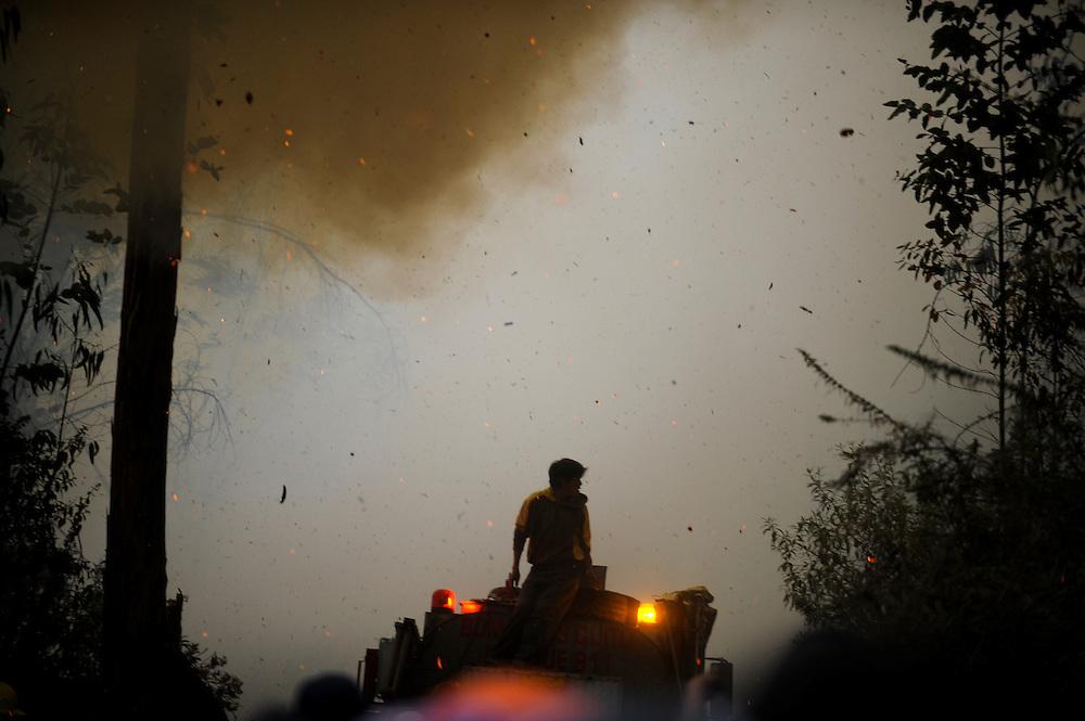 El viento arroja cenizas y astillas en llamas hacia un joven que miraba un incendio desde la cima de un carro de bomberos en el parque metropolitano de Quito. Durante una sequía de dos meses, aproximadamente 2565 incendios forestales, (muchos presuntamente provocados) quemaron 3796 hectareas de bosques, algunas casas y muchos animales silvestres en las laderas boscosas que rodean Quito, la capital del Ecaudor.   Ningún humano murió, pero tomaran décadas antes de que las áreas afectadas se recuperen.