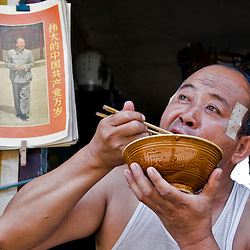 Chinesse man eating with chopsticks in his shop. Pingyao, Shanxi, China.