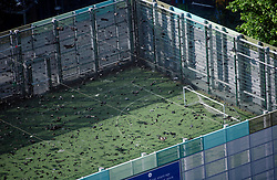 © Licensed to London News Pictures. 14/06/2017. London, UK. Debris and ash lying on a nearby football pitch at the scene of a huge fire at Grenfell tower block in White City, London. The blaze engulfed the 27-storey building with 200 firefighters attending the scene. There were reports of people trapped in the building. Photo credit: Ben Cawthra/LNP