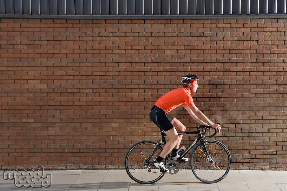 Man cycling past brick wall