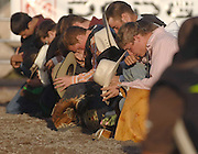 "Bull riders take a knee and remove their hats for the saying of the ""Cowboys Prayer"" prior to start of the Excalibur Rodeo at the 2009 Emmet-Charlevoix County Fair."