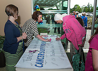 Marketing Coordinator Liane Clairmont and Communications Associate Sarah Lapointe welcome Raye Masse (8 months) as she signs the banner during LRGH Cancer Survivor Day held Tuesday afternoon.  (Karen Bobotas/for the Laconia Daily Sun)