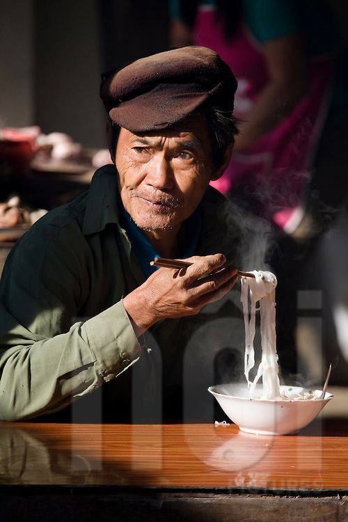 Portrait of an elderly vietnamese man eating a noodle soup in a local restaurant of Mai Chau, Hoa Binh Province, Vietnam, Southeast Asia