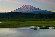 Mount Adams is partially reflected in Trout Lake. The reflection is distorted by strong winds that blew across the water. At 12,276 feet, Adams is the second-tallest peak in Washington..