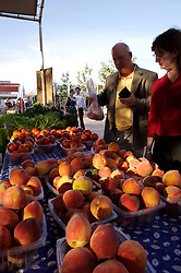 Stock photo of shoppers buying peaches and tomatoes at the organic market in the park