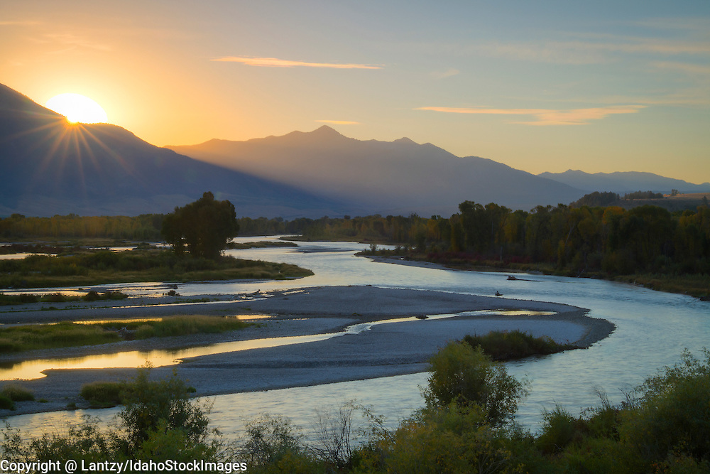 Idaho, Eastern, Swan Valley. South Fork of the Snake River as the sun crests the Wind River Range on an autumn morning.