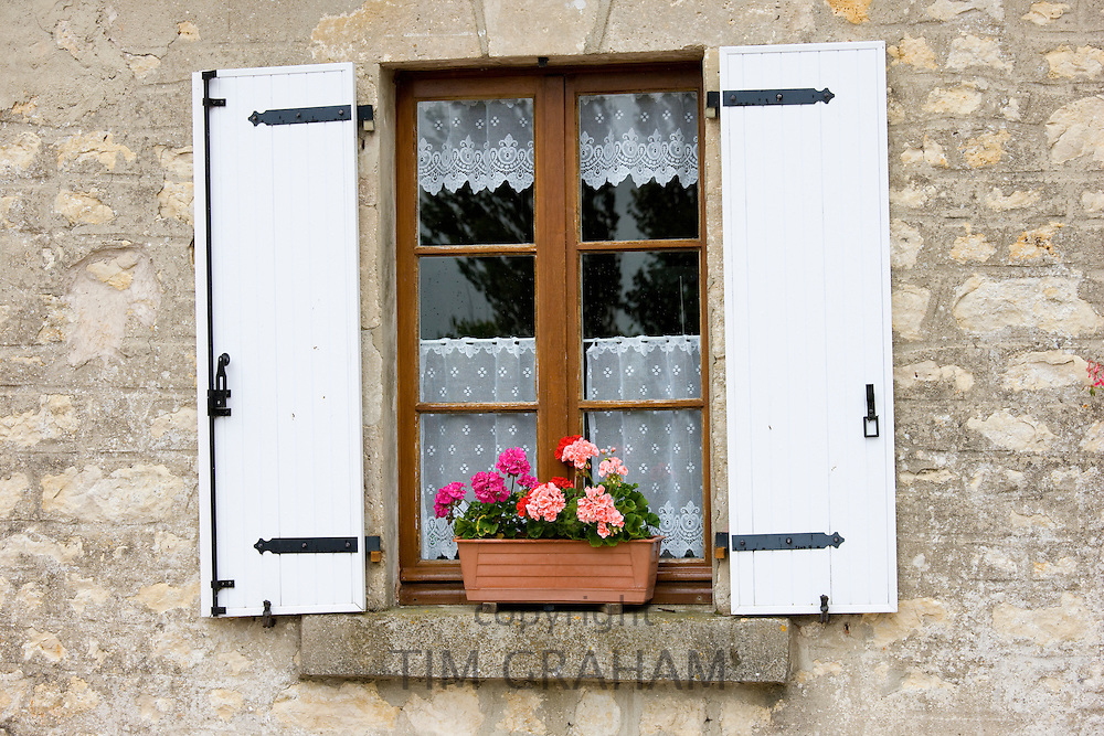 Typical French window with lace curtain and pelmet, window box and wooden shutters, Normandy, France