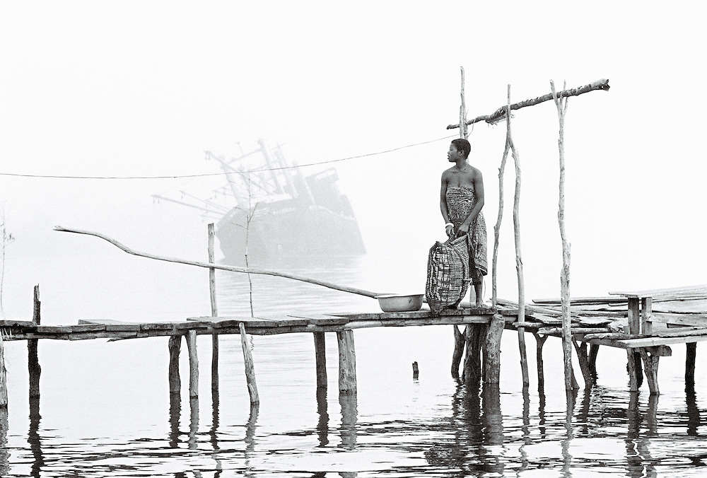 River Niger delta, Bendel State, Nigeria. Woman on wooden jetty at Bennett Island Anchorage on the Warri River shipping channel.