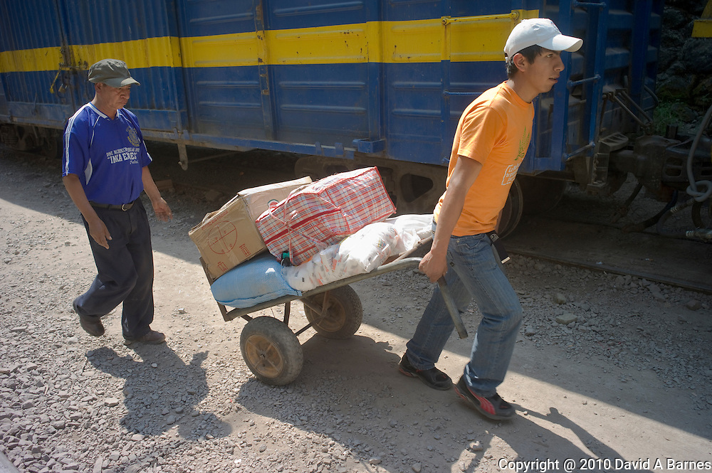 Man puling freight on a dolly unloading a train, Agua Calientes, Peru