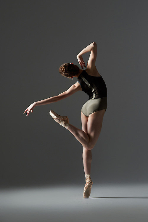 Classical female ballet dancer, Isabelle Macgill, in a green leotard, taken on dark gray background. Photograph taken in New York City by photographer Rachel Neville.