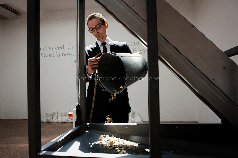 VENICE, ITALY - 29 MAY 2013: A performer pours Danae coins that will then be dropped to the lower level towards the women with umbrellas, at the Russian Pavillon, Giardini of the Biennale in Venice, Italy, on May 29th 20113. <br /> <br /> Vadim Zakharov's Danae project has united the upper and lower storeys of the Pavillon in a single project for the first time in the building's long history, built in 1914. The theme of the installation turns around the ancient Greek myth of Danae. Vadim Zakharov states: &quot;The installation has two points for viewing - from above and from below. Kneeling and looking down, we can grasp and feel that we are present at a unique process of materialization of the myth. Though the huge hole in the floow, we fall into another semantic and poetic space, into which golden coins fly from a pyramid ceiling. Below we see women with umbrellas, which protect them from being struck by the coins. The lower hall can only be visited by women. This is not about sexism but merely follows the logic of the anatomical construction of the myth. What is masculine can only fall inside from above, in the form of golden rain. The lower level of the Pavillon is &quot;cave womb&quot;, keeping tranquility, knowledge, and memory intact.<br /> <br /> The 55th International Art Exhibition of the Venice Biennale takes place in Venice from June 1st to November 24th, 2013 at the Giardini and at the Arsenale as well as in various venues the city. <br /> <br /> Gianni Cipriano for The New York TImes