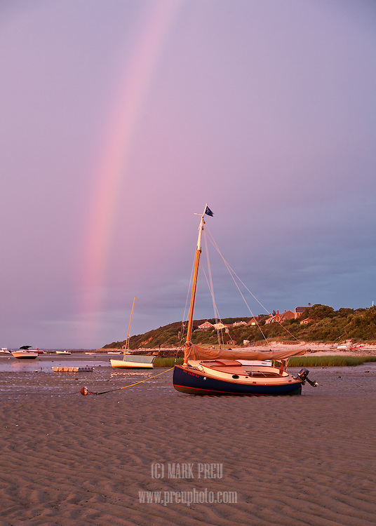 A rainbow arches over boats resting on the flats at Saint's Landing in Brewster.