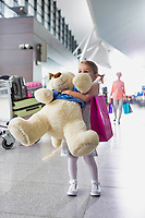 Portrait of young little girl holding her big teddy bear in airport