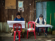 20 MAY 2017 - BANGKOK, THAILAND: Architectural students sketch homes in Pom Mahakan. Students of architecture working under the auspices of Vernadoc, an organization that documents historic structures and communities in Thailand, are documenting the historic homes in Pom Mahakan. Bangkok city officials are expected to tear the structure down in coming weeks. The final evictions of the remaining families in Pom Mahakan, a slum community in a 19th century fort in Bangkok, have started. City officials are moving the residents out of the fort. NGOs and historic preservation organizations protested the city's action but city officials did not relent and started evicting the remaining families in early March.        PHOTO BY JACK KURTZ