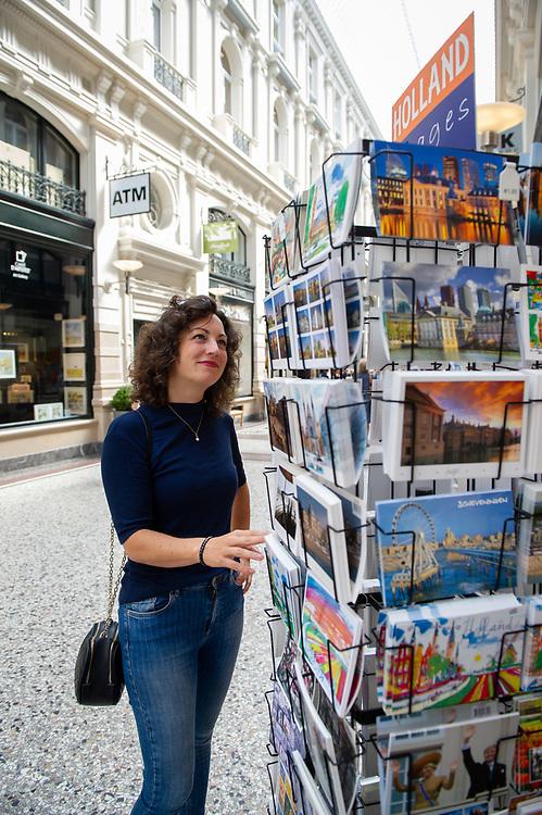 Den Haag. Passage. Een jonge vrouw bekijkt ansichtkaarten.   Foto: Gerrit de Heus. The Netherlands. A young woman looking at postcards. Photo: Gerrit de Heus.