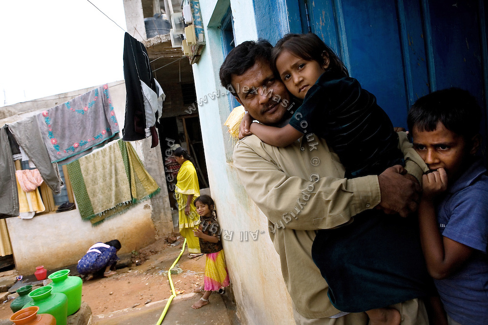 Shafiq Syed, 34, is holding her daughter Simran, 7, in front of their home in a poor neighbourhood of Bangalore, Karnataka, India, while his elder son Waseem, 11, is standing by. Shaifq has been the main character of the Cannes' Camera D'Or 1988 winner Salaam Bombay, but after the movie he failed to become a star, fell back into poverty and lived on the streets for years before he became a rickshaw (tuk-tuk) driver in his home city of Bangalore, Karnataka State, India.