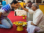 17 AUGUST 2014 - BANGKOK, THAILAND:     A Hindu priest anoints a man during Krishna Janmashtami services at the Vishnu temple in Bangkok. Krishna Janmashtami is the annual celebration of the birth of the Hindu deity Krishna, the eighth avatar of the Hindu god Vishnu. It is celebrated by Hindus in Thailand. There are about 53,000 Hindus in Thailand, most originally from India, but many Hindu deities are highly revered by Thai Buddhists and Hindu holy days are observed by many Thai Buddhists.  PHOTO BY JACK KURTZ