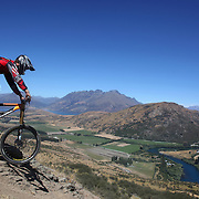 Sam Perry from Leeston in action during the NZBNZ South Island Downhill Cup mountain bike downhill series held on The Remarkables face with a stunning backdrop of the Wakatipu Basin. 150 riders took part in the two day event.  Queenstown, Otago, New Zealand. 9th January 2012. Photo Tim Clayton