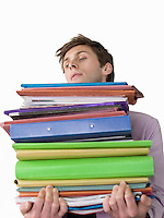Male office worker carrying heavy binders close-up